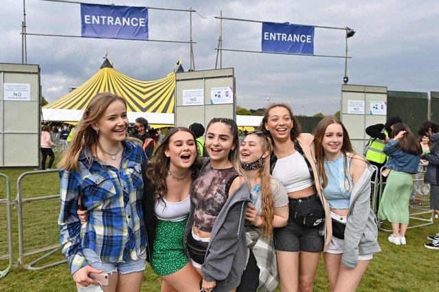 Concert-goers pose for a photograph as they arrive at the venue for the latest event in the government's Events Research programme, a live music concert hosted by Festival Republic in Sefton Park in Liverpool, north-west England on May 2, 2021, where a non-socially-distanced crowd of 5,000 are expected to attend. A pilot programme to examine ways of putting on events in a post-covid-19 world will include a concert by the band Blossoms which will do away with social distancing, though audience members will have to provide proof of a negative coronavirus test before gaining entry. (Photo by Paul Ellis/AFP Photo)