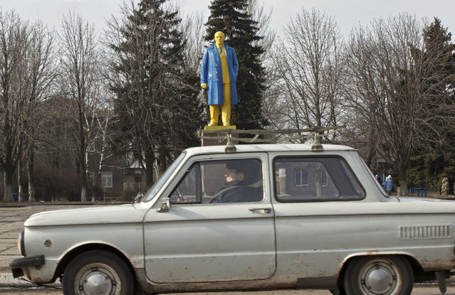 A man rides in a car by a statue of Lenin, painted in the colors of Ukraine's national flag, in Velyka Novosilka, Ukraine, Thursday, February 19, 2015, near the border between Russia backed rebels and Ukrainian held territories, on the Ukrainian side. (Photo by Vadim Ghirda/AP Photo)