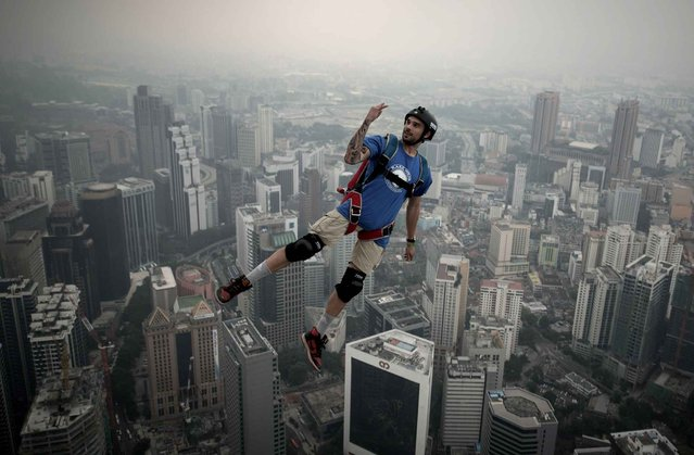Base jumper Theo Gagliardini from France leaps from the 300-meters Open Deck of the Malaysia's landmark Kuala Lumpur Tower during the International Tower Jump in Kuala Lumpur on September 27, 2013. (Photo by Mohd Rasfan/AFP Photo)