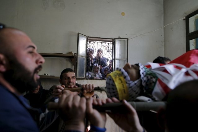 "Palestinian women look through a window as mourners carry the body of Palestinian Srur Abu Srur, who was killed by Israeli army on Tuesday, during his funeral in Aida refugee camp in the West Bank city of Bethlehem January 13, 2016. The Palestinian Health Ministry said Abu Srur, 21, was killed by Israeli army gunfire during a confrontation between troops and protesters in the town of Beit Jalla, near Bethlehem. The military said troops had fired at ""rioters who hurled firebombs and rocks at the soldiers"". (Photo by Ammar Awad/Reuters)"