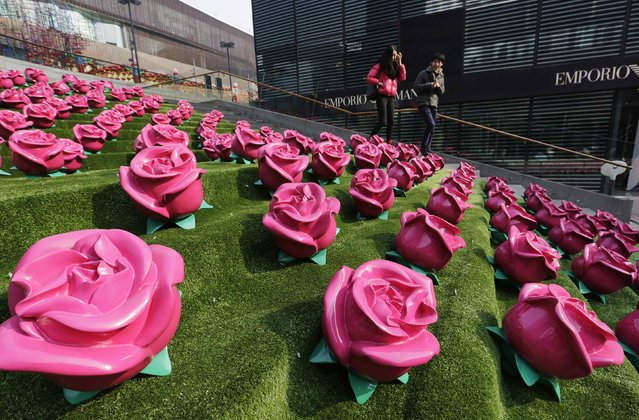 A couple walk past an installation art work of roses at a shopping centre on Valentine's Day, in Beijing February 14, 2015. (Photo by Jason Lee/Reuters)