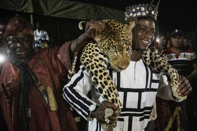 """Members of the Association of Dozos of Dafra carry the body of a leopard during a celebration of their culture in Bobo-Dioulasso, Burkina Faso, 360 kilometers (220 miles) west of the capital, Ouagadougou, on Sunday, March 28, 2021. """"Before someone faces a challenge, they know there are supernatural powers and spirits they can call upon in any situation"""", said Jean Celestin Ky, professor of history at Joseph Ki-Zerbo University in Ouagadougou. (Photo by Sophie Garcia/AP Photo)"""
