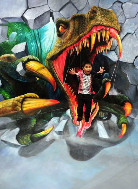 A child poses for photos with a 3D painting at a 3D experiencing gallery in Tianjin, China, on October 3, 2013. (Photo by Xinhua/Landov/Barcroft Media)