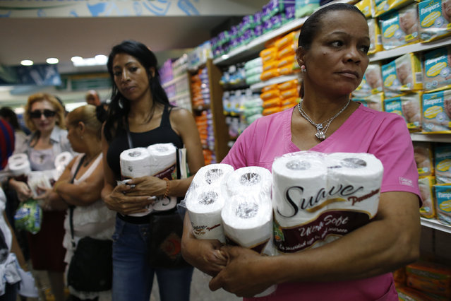 Women wait in line as they buy toilet paper at a supermarket in Caracas, May 17, 2013. (Photo by Jorge Silva/Reuters)
