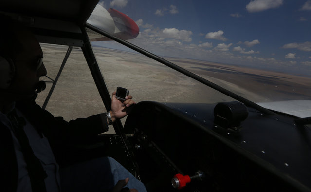 In this January 16, 2016 photo, a plane flies over the dry lake bed of Lake Poopo, Bolivia. The El Nino weather phonomenon has inflicted periodic droughts on Poopo for millennia and last struck this hard in 1997-98. But over the past three decades unprecedented stress has befallen a fragile ecosystem where 83 percent of rainfall evaporates. (Photo by Juan Karita/AP Photo)