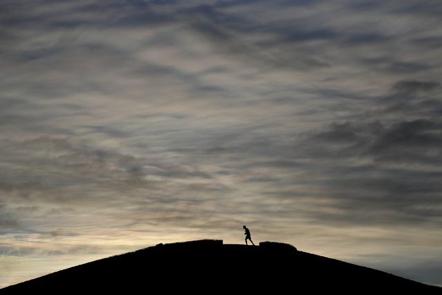 A jogger takes an early morning run as lockdown measures start to be lifted in London, Tuesday, April 6, 2021. Temperatures dropped to –7C (19.4F) in some parts of the UK overnight as Arctic winds brought an end to the good weather. (Photo by Kirsty Wigglesworth/AP Photo)