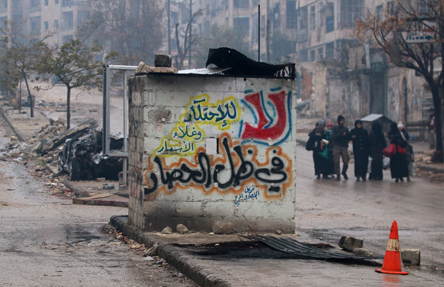 """People carry their belongings as they flee deeper into the remaining rebel-held areas of Aleppo, Syria December 13, 2016. The Arabic words read, """"No to monopolizing commodities and raising prices under the siege"""". (Photo by Abdalrhman Ismail/Reuters)"""