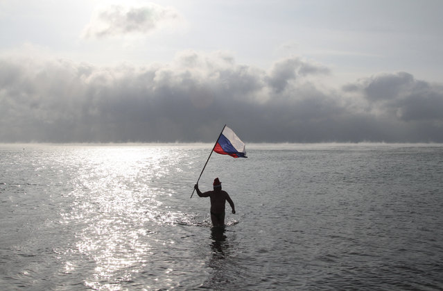 A man holds a Russian national flag while walking out of the cool waters of the Black Sea, as fans of winter swimming gather on a beach on the Orthodox Christmas day in the port of Yevpatoriya, January 7, 2015. (Photo by Pavel Rebrov/Reuters)