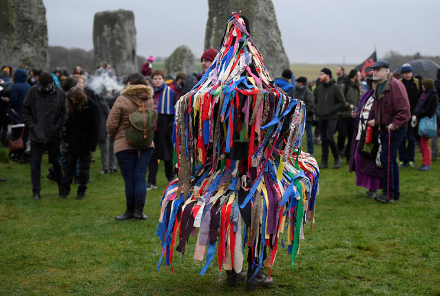 Visitors and revellers react amongst the prehistoric stones of the Stonehenge monument at dawn on Winter Solstice, the shortest day of the year, near Amesbury in south west Britain, December 21, 2016. (Photo by Toby Melville/Reuters)