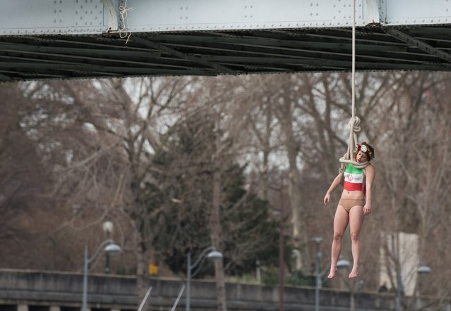 A Femen activist, Sarah Constantin, is hanged from a noose-like rope from a Paris bridge to call attention to the large number of executions in Iran as she stages a protest against visiting Iranian President Hassan Rouhani in Paris, Thursday, January 28, 2016. A near-naked woman hanging from a noose-like rope from a Paris bridge has sent a message to visiting Iranian President Hassan Rouhani. (Photo by Zacharie Scheurer/AP Photo)