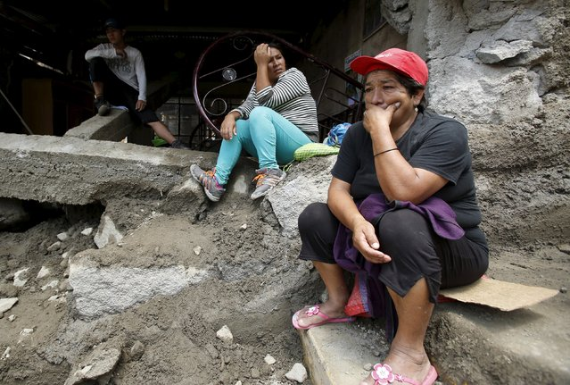 A woman and her family sit outside their destroyed houses after a massive landslide in Chosica, March 24, 2015. (Photo by Mariana Bazo/Reuters)