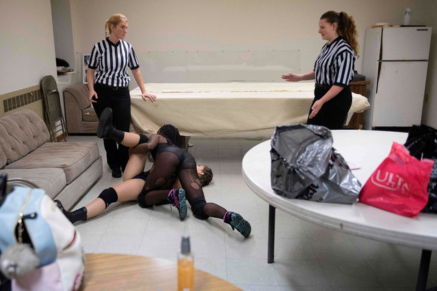 MCW referee Beckie Phillips (L) and another referee (R) go through professional wrestler Gia Scott (C) and Aria Palmer' s match backstage in a makeshift dressing room at a firehouse in Galena, Maryland, on October 6, 2018, prior to Autumn Armageddon 2018 to work out what will happen during the match and get their timing down. (Photo by Jim Watson/AFP Photo)