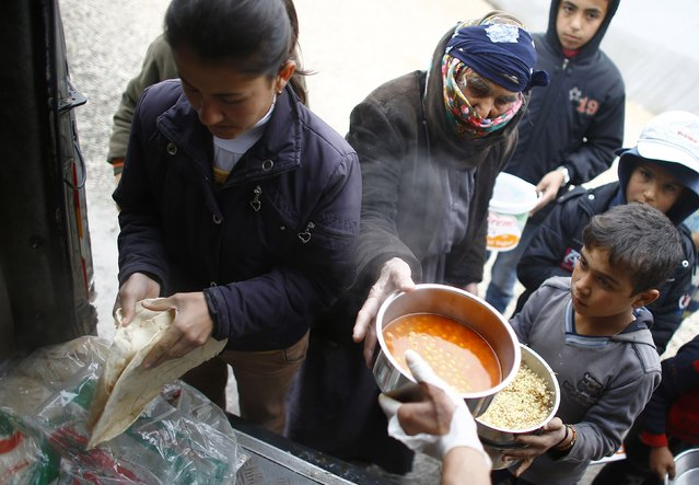 Kurdish refugees from the Syrian town of Kobani wait for food distributed during lunch time at a refugee camp in the border town of Suruc, Sanliurfa province January 31, 2015. (Photo by Umit Bektas/Reuters)
