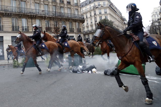 Mounted Police officers on their horses take their positions during clashes with yellow-vested protesters, in Paris, France, Saturday, December 8, 2018. Crowds of protesters angry at President Emmanuel Macron and France's high taxes tried to converge on the presidential palace Saturday, some scuffling with police firing tear gas, amid exceptional security measures aimed at preventing a repeat of last week's rioting. (Photo by Thibault Camus/AP Photo)