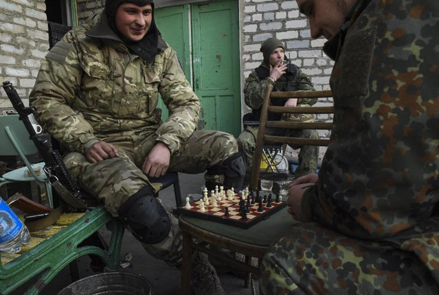 Fighters of the Azov Battalion play chess during a break in the town of Shyrokyne, eastern Ukraine, Sunday, March 22, 2015. (Photo by Mstyslav Chernov/AP Photo)