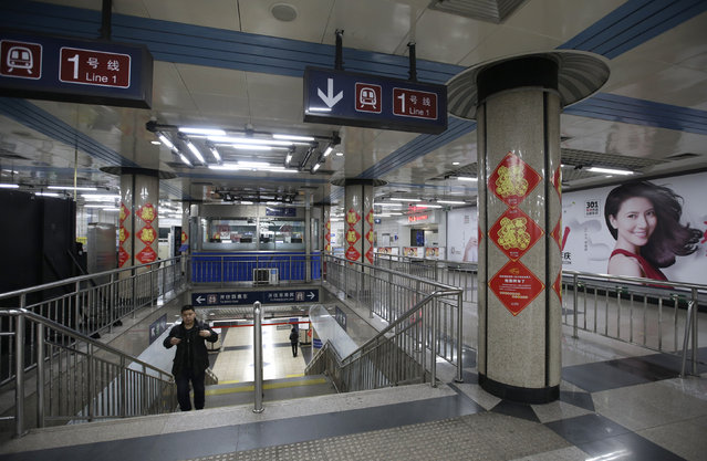 A passenger walks out of a station of the Subway Line Number 1 on the eve of the Chinese Lunar New Year, in Beijing, China, February 7, 2016. (Photo by Jason Lee/Reuters)
