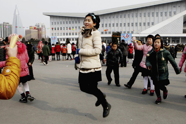 North Korean students skip rope as they gather on the plaza in front of the ice rink for Lunar New Year in Pyongyang, North Korea, Monday, February 8, 2016. (Photo by Jon Chol Jin/AP Photo)