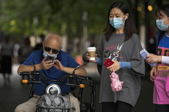 Women wearing face masks to help curb the spread of the coronavirus walk past a masked man browsing his smartphone on his bike in Beijing, Tuesday, July 20, 2021. (Photo by Andy Wong/AP Photo)
