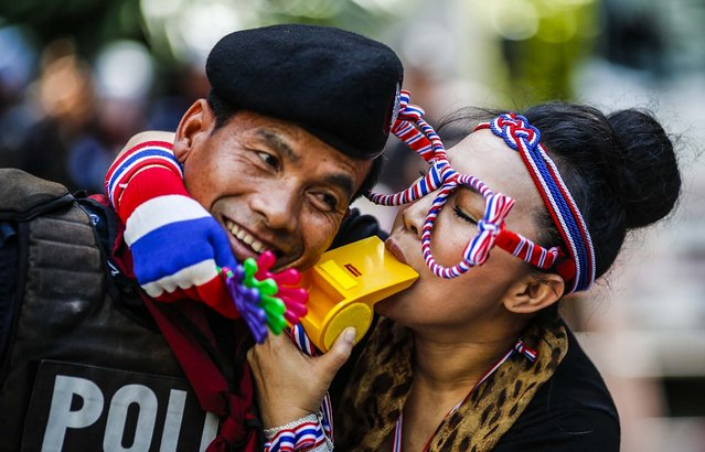 An anti-government protester blows on a whistle next to a riot policeman as she gathers with others outside the headquarters of the ruling Puea Thai Party of Prime Minister Yingluck Shinawatra in Bangkok, on November 29, 2013. (Photo by Athit Perawongmetha/Reuters)