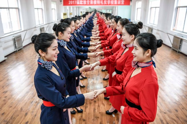 Students attend a stewardess skill training for the upcoming 2017 entrance examination for art majors in colleges in Luoyang, central China's Henan Province, January 4, 2017. The proper way to shake hands when greeting people is also coached in the intensive course. (Photo by Li Bo/Xinhua/Barcroft Images)