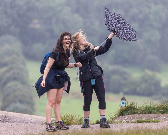 Hikers, left, Sarah Done 24 and Catherine Edwards enjoy a climb up Box Hill during Storm Evert in Surrey in South East England on July 30, 2021. Storm Evert is the UK's fourth named storm since October 2020. (Photo by London News Pictures)