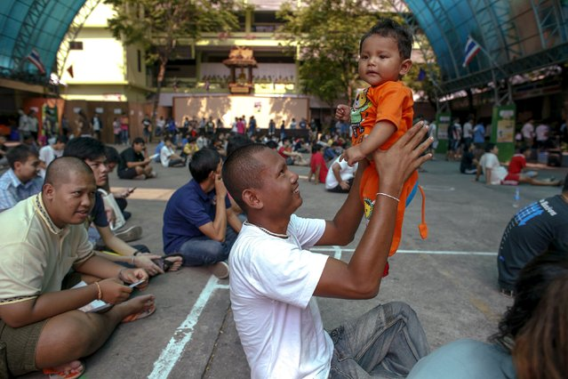 Sithiphan, 21, spends time with his son during an army draft held at a school in Klong Toey, the dockside slum area in Bangkok April 5, 2015. (Photo by Athit Perawongmetha/Reuters)