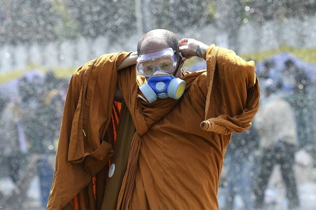 A Thai Buddhist monk puts on a gas mask as riot police use water cannon and tear gas while anti-government protesters attempt to remove barricades outside Government House in Bangkok December 2, 2013. Thai protesters took to the streets on Monday to renew their fight to topple Prime Minister Yingluck Shinawatra, prompting riot police to fire teargas and stun grenades for a second day outside her fortified office compound to keep them at bay. (Photo by Dylan Martinez/Reuters)