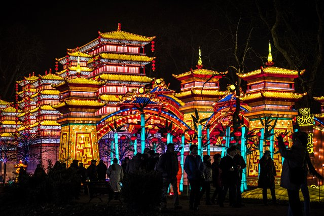 Visitors stand in front of monumental silk lanterns depicting a palace, installed at the Foucaud Park in Gaillac, southwestern France, during the Lantern Festival, on December 12, 2018. Monumental silk sculptures are exhibited in Gaillac from December 1, 2018 to February 6, 2019, as part of the Chinese traditional Lantern Festival marking the end of celebrations for the Chinese Lunar New Year period. (Photo by Eric Cabanis/AFP Photo)