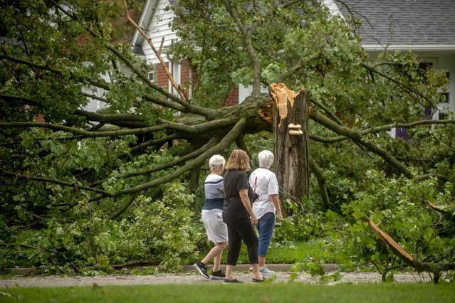 Flushing residents Donna Black, from left to right, Brenda Nyquist and Judy Doyle looks at the damage around their neighborhood as they check in with neighbors health and well-being on Thursday, August 12, 2021 in Flushing, Mich., after a wave of strong storms ravaged neighborhoods in parts of Genesee County on Wednesday night. Heavy rains are bringing flooding to parts of Michigan, as waves of thunderstorms make their way across the Midwest. (Photo by Jake May/The Flint Journal via AP Photo)