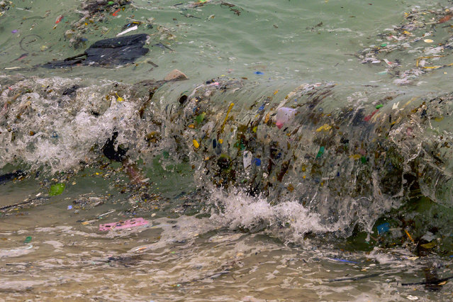 A wave carrying plastic waste and other rubbish washes up on a beach in Koh Samui in the Gulf of Thailand on January 19, 2021. (Photo by Mladen Antonov/AFP Photo)