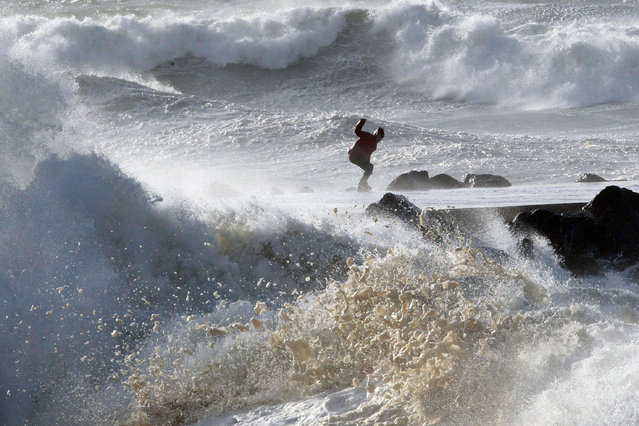 A man tries to keep his balance as waves hit the seawall at the beach in Anglet, southwestern France, Friday, January13, 2017. (Photo by Bob Edme/AP Photo)