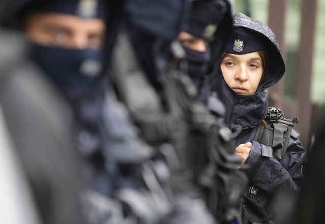 Police ensure a peaceful protest, as protesters chained themselves to the fence surrounding the headquarters of Poland's Border Guards and put barbed wire on top of the fence to protest the government's refusal to let in a group of illegal migrants,  in Warsaw, Poland, Monday, August 23, 2021. The group of migrants have been stuck in the open air at the border with Belarus for two weeks.(Photo by Czarek Sokolowski/AP Photo)