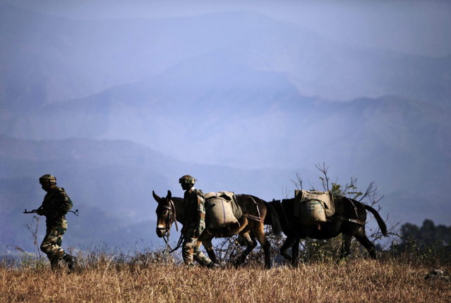 In this Monday, December 23, 2013 photo, Indian army soldiers walk with ponies carrying food supply to one of their forward posts near the Line of Control (LOC), that divides Kashmir between India and Pakistan, at Krishna Ghati (KG Sector) in Poonch, 290 kilometers (180 miles) from Jammu, India. The military commanders of longtime rivals India and Pakistan met on Tuesday in a bid to stop frequent cross-border attacks in disputed Kashmir which escalated tensions in the region in recent months. (Photo by Channi Anand/AP Photo)