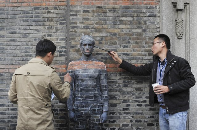 Artists apply paint on a man blending himself into the background in front of the wall of an ancient building in Shanghai, April 10, 2015. Several local artists demonstrate in this form on the street to raise awareness of the protection of traditional constructions in the city of Shanghai, local media reported. (Photo by Reuters/Stringer)
