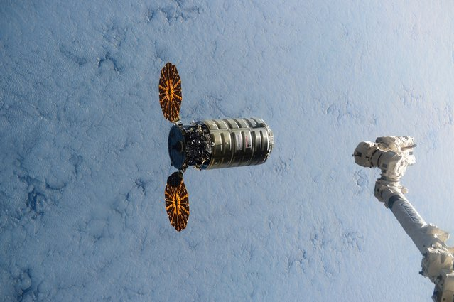 This image made available by NASA via Twitter shows the Cygnus spacecraft approaching the International Space Station on Wednesday, December 9, 2015. At right is the station's robot arm. The capsule brought over 3 tons of cargo. (Photo by Scott Kelly/NASA via AP Photo)