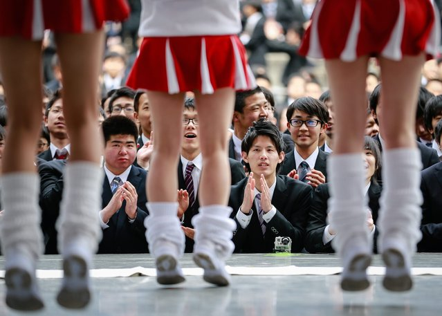 Japanese college graduates watch cheerleaders on stage during a job hunting rally at a park in downtown Tokyo, Japan, 25 February 2016. Some 1,500 college graduates from various Japanese vocational schools attended the pep rally in an effort to gain positive enthusiasm for the upcoming job hiring season in Japan. (Photo by Christopher Jue/EPA)