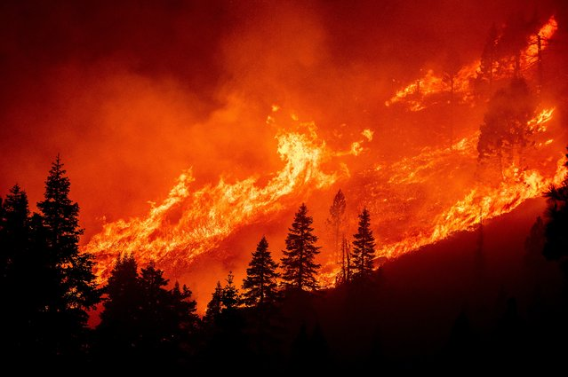 Seen from South Lake Tahoe, Calif., flames from the Caldor Fire leap along a hillside above Christmas Valley on Monday, August 30, 2021. (Photo by Noah Berger/AP Photo)
