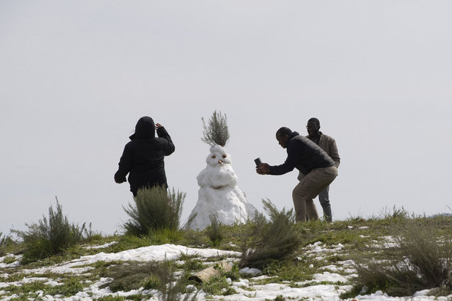 People take pictures of a snowman after unusually heavy snowfalls in the mountains and highlands above the town of Ceres, about 180km from Cape Town on August 29, 2021. (Photo by Rodger Bosch/AFP Photo)