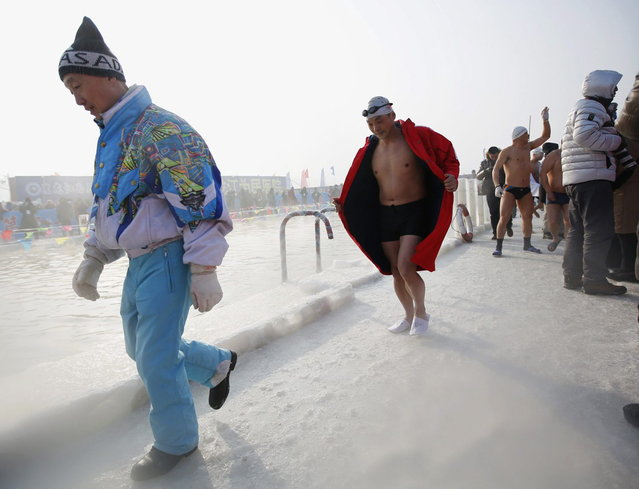 A swimmer follows an official from the organiser to his platform on a pool carved into the thick ice covering the Songhua River during the Harbin Ice Swimming Competition in the northern city of Harbin, Heilongjiang province January 5, 2014. (Photo by Kim Kyung-Hoon/Reuters)