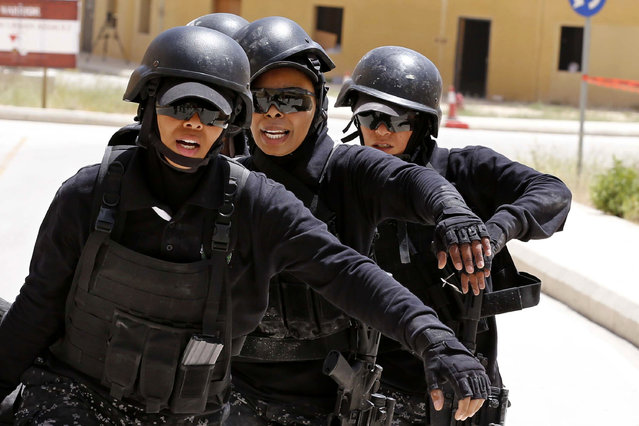 Members of the Jordanian women's police special operations team wait to compete during the 7th Annual International Warrior Competition hosted by the King Abdullah Special Operations Training Center (KASOTC), in Amman, Jordan, Tuesday, April 21, 2015. Jordan is hosting a competition of elite anti-terrorism squads from 18 countries, including fellow members of the military coalitions fighting rebels in Yemen and Islamic State extremists in Iraq and Syria. (Photo by Raad Adayleh/AP Photo)