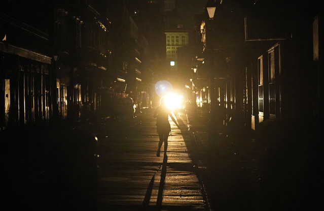 A police officer patrols past woman walking along Bourbon Street in the French Quarter after Hurricane Ida knocked out power to the city, Monday, August 30, 2021, in New Orleans, La. (Photo by Eric Gay/AP Photo)