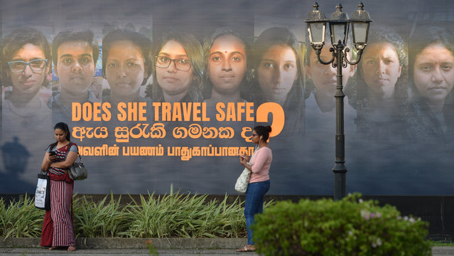 Women stand near a banner of an International Women's day photo exhibition in Colombo on March 7, 2019, ahead of International Women's Day, which is celebrated every year on March 8. (Photo by Ishara S. Kodikara/AFP Photo)