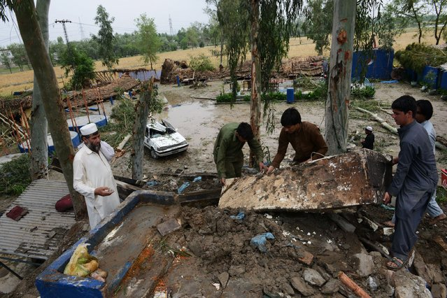Pakistani residents collect belongings at their home after it was damaged in heavy rain and winds in Peshawar on April 27, 2015. (Photo by A. Majeed/AFP Photo)