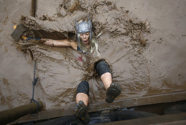A competitor falls in to muddy water during the Tough Guy event in Perton, central England, January 26, 2014. The annual event to raise cash for charity challenges thousands of international competitors in a cross country run followed by an assault course consisting of obstacles including water, fire and tunnels. (Photo by Darren Staples/Reuters)