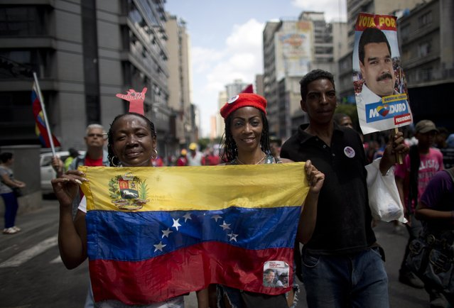 """Supporters of Venezuela's President Nicolas Maduro holds a national flag as they take part in an anti-imperialist march in Caracas, Venezuela, Saturday, March 16, 2019.  Many were clad in red, the color associated with the movement led by Chavez, the former military officer who declared a socialist """"revolution"""" after coming to power in 1999. (Photo by Ariana Cubillos/AP Photo)"""