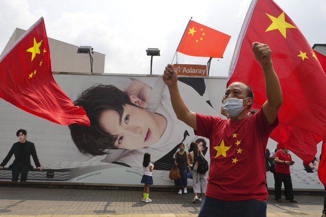 A man waves Chinese national flag in front of a huge poster of Anson Lo, Hong Kong singer and a member of the Hong Kong boy group Mirror after a ceremony to mark China's 72nd National Day in Hong Kong Friday, October 1, 2021. (Photo by Vincent Yu/AP Photo)