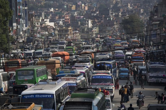 Buses loaded with Nepalese people going to their hometowns prepare to leave Kathmandu, Nepal, Wednesday, April 29, 2015. Thousands of people are lining up at bus stations in Kathmandu where the government is providing free transportation for people hoping to travel to their hometowns and villages. (Photo by Bernat Amangue/AP Photo)