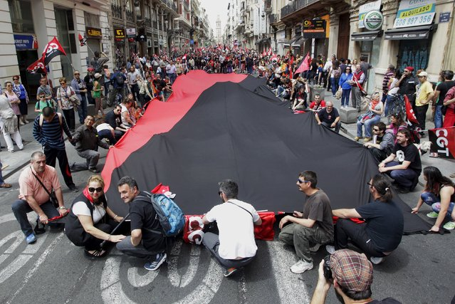 Demonstrators of the General Confederation of Work (CGT) lay down a giant flag during May Day celebrations in Valencia, Spain, May 1, 2015. (Photo by Heino Kalis/Reuters)