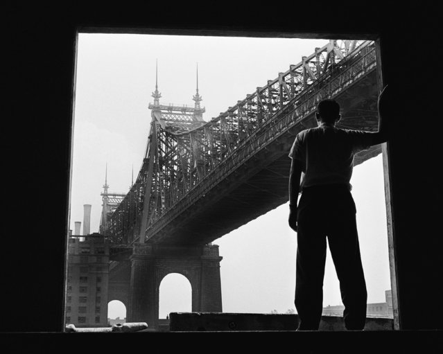 Framed in the archway of a building, a passerby stops to look at the broad span of the Queensboro Bridge from New York City's East River shore line on August 19, 1959. The passerby is none other than the photographer himself, Robert Goldberg, who used a self timer to get himself in the picture. (Photo by Robert Goldberg/AP Photo)