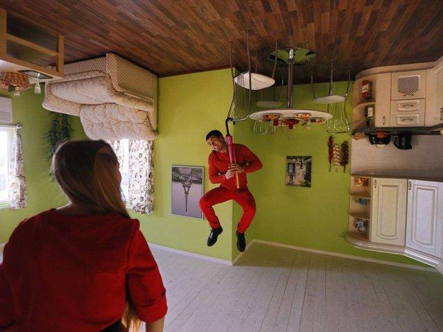 "Visitors admire the ""Upside Down House"". (Photo by Yuri Kochetkov/EPA)"